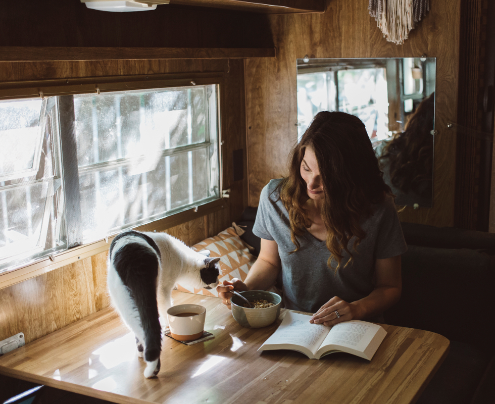 Woman eating breakfast with cat on table in cabin