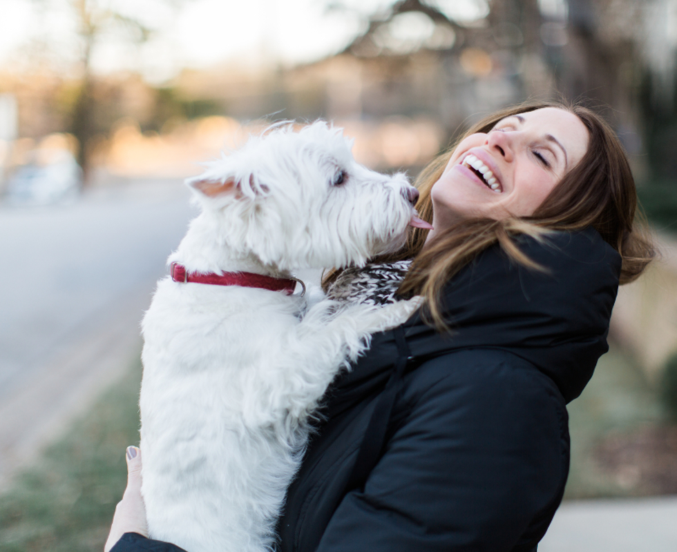 Woman holding dog laughing